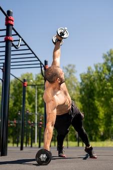 Jonge gespierde bodybuilder training buiten op sportveld tijdens het tillen van zware halter tijdens het sporten
