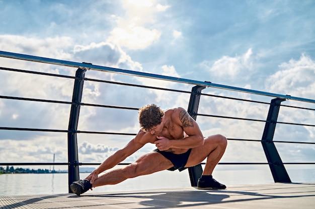 Jonge gespierde getatoeëerde man doet oefeningen die zich vroeg in de ochtend uitstrekken op de pier bij de zee