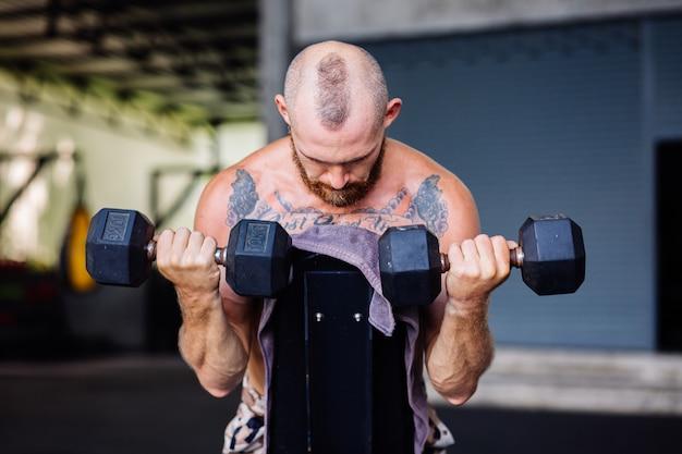 Jonge gespierde getatoeëerde sterke spier bebaarde europese man doet zware oefening