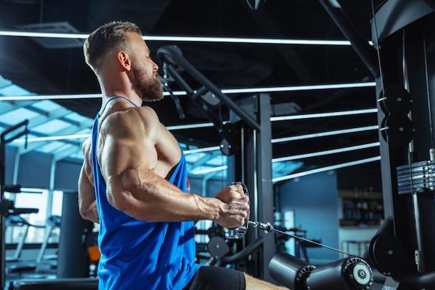 Jonge gespierde kaukasische atleet trainen in de sportschool, krachtoefeningen doen, oefenen, werken aan zijn bovenlichaam, gewichten en halters trekken. fitness, wellness, gezond levensstijlconcept, werken.