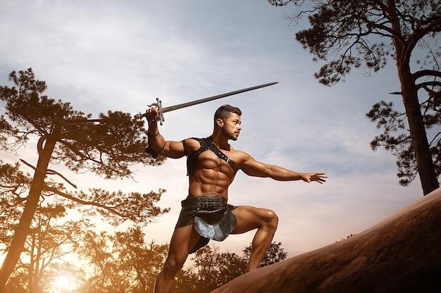Jonge gespierde krijger met een zwaard in de bergen