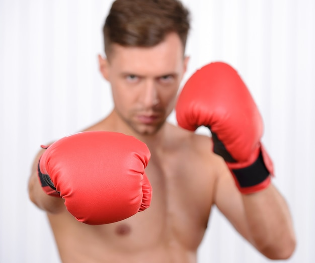 Jonge gespierde man bokser training in bokshandschoenen.