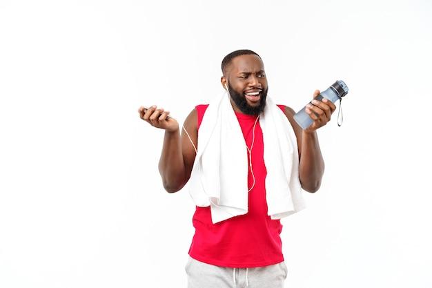 Jonge gespierde man houdt fleswater vast na het hardlopen, aantrekkelijke atleet rust na training buitenshuis, fitness en gezond levensstijlconcept. geïsoleerd op wit.
