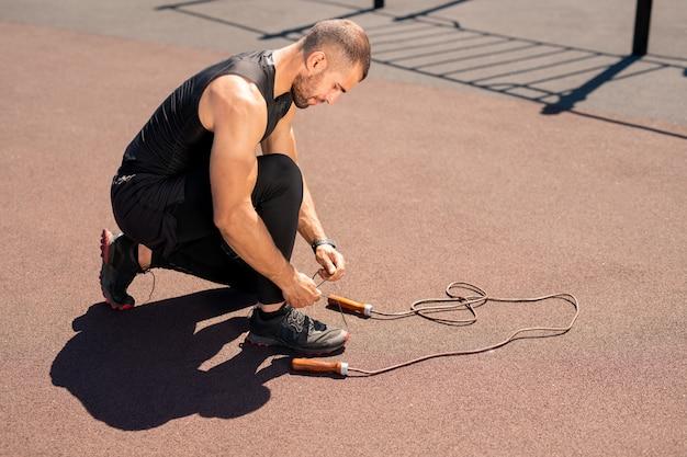 Jonge gespierde man in zwarte sportkleding bukken sneaker terwijl schoenveter op sportveld binden voordat u gaat trainen