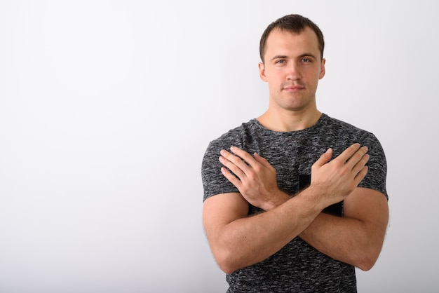 Jonge gespierde man met beide armen gekruist op de borst