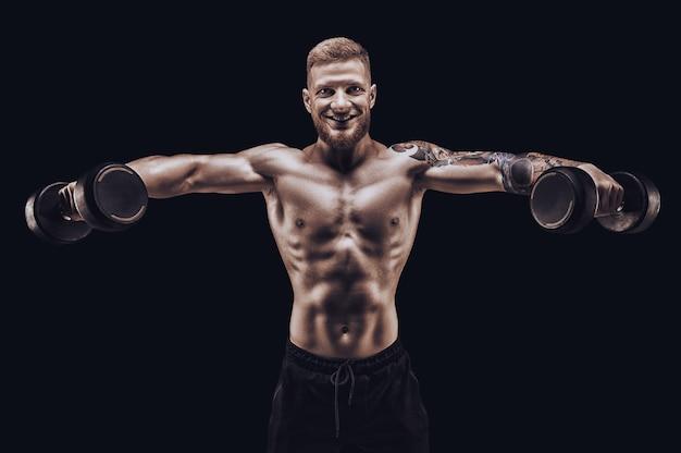Jonge gespierde man pompt delta's met halters op een zwarte achtergrond. fitness en voeding concept. gemengde media Premium Foto