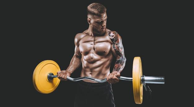 Jonge gespierde man pompt zijn biceps met een barbell op een zwarte achtergrond. fitness en voeding concept. gemengde media