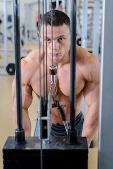 Jonge gespierde man trainen in de sportschool