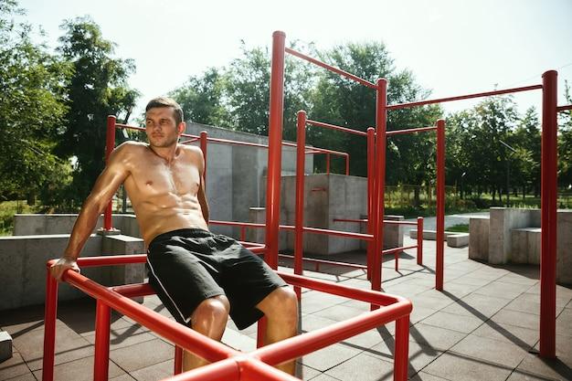 Jonge gespierde shirtless blanke man doet crunches op horizontale balk op speelplaats in zonnige zomerdag. bovenlichaam buiten trainen. concept van sport, training, gezonde levensstijl, welzijn.