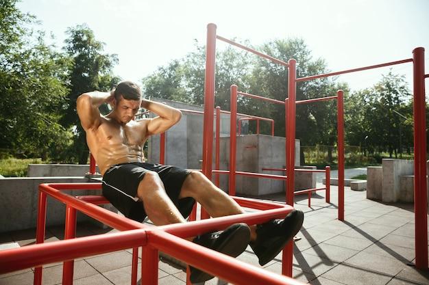 Jonge gespierde shirtless blanke man doet crunches op horizontale balk op speelplaats in zonnige zomerdag