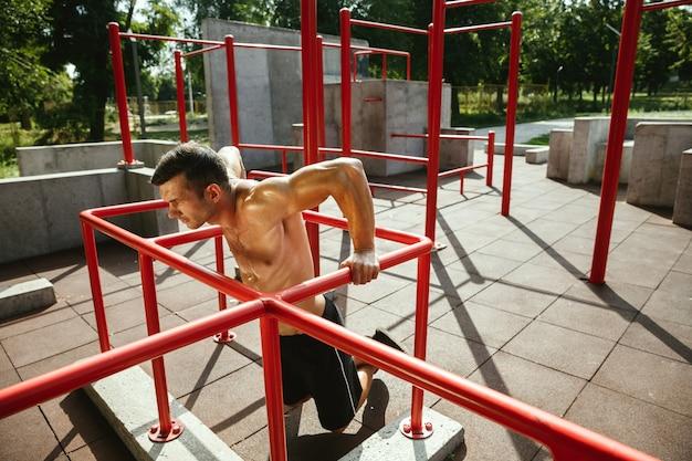 Jonge gespierde shirtless blanke man doet pull-ups op horizontale balk op speelplaats in zonnige zomerdag. zijn bovenlichaam buiten trainen. concept van sport, training, gezonde levensstijl, welzijn.