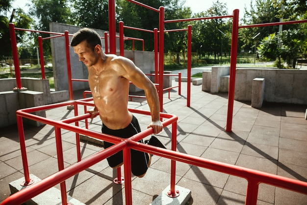 Jonge gespierde shirtless blanke man doet pull-ups op horizontale balk op speelplaats in zonnige zomerdag