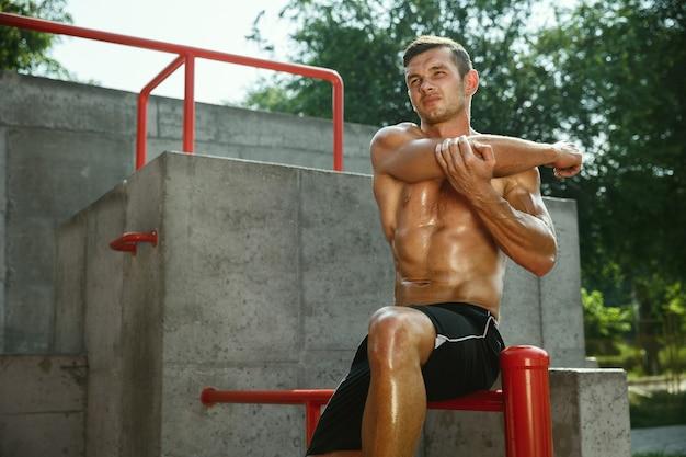 Jonge gespierde shirtless blanke man doet rekoefeningen op de speelplaats in zonnige zomerdag.