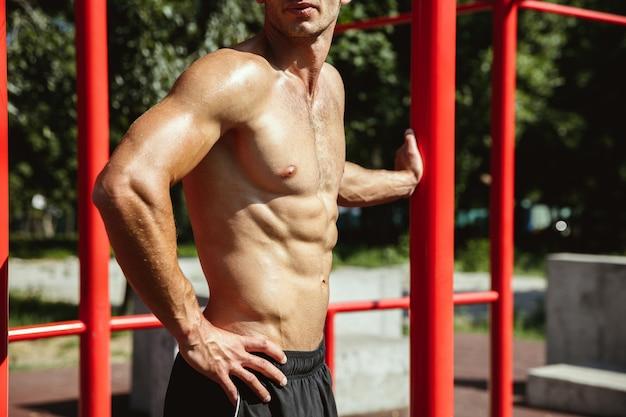 Jonge gespierde shirtless blanke man tijdens zijn training op horizontale balken op de speelplaats in zonnige zomerdag. zijn lichaam buiten trainen. concept van sport, gezonde levensstijl, welzijn.