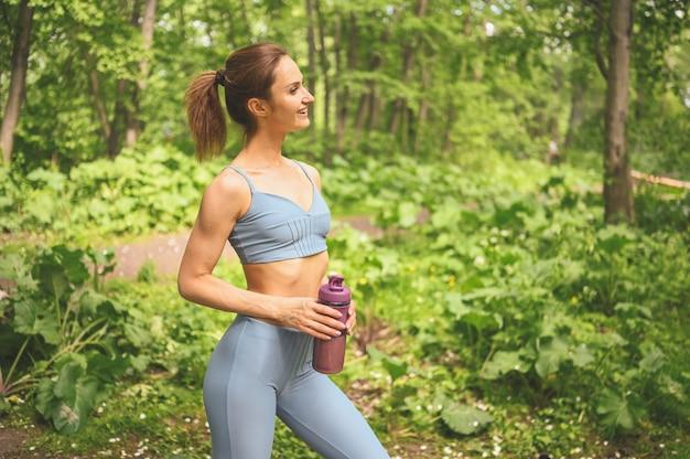 Jonge gespierde slim fit vrouw met platte buik in blauwe sportkleding houden fles water doet sport en fitness in de zomer park buiten