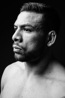 Jonge gespierde spaanse man shirtless op zwart
