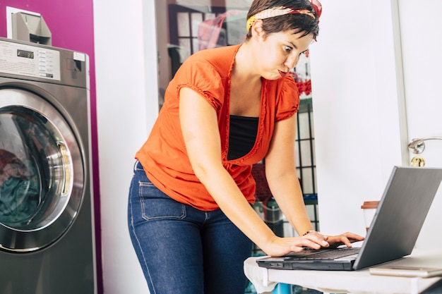 Jonge gestresste dame aan het werk in de automatische winkel van de wasmat - snuiven en problemen oplossen met een notebookcomputer en internetbedrijf - nieuw concept van werk voor millennials gebruiken technlo