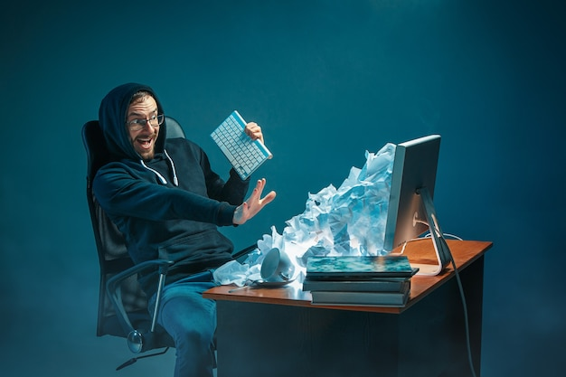 Jonge gestresste knappe zakenman die aan het bureau in een modern kantoor werkt, schreeuwt op het laptopscherm en is boos over e-mailspam. collage met een berg verfrommeld papier. zakelijk, internetconcept