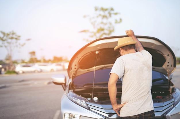 Jonge gestresste man die problemen heeft met zijn stress kapotte auto machinekamer crash bij defecte motor wacht op hulp.