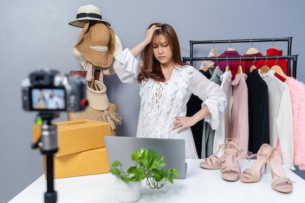 Jonge gestresste vrouw die kleding en accessoires online verkoopt door camera livestreaming, zakelijke online e-commerce thuis
