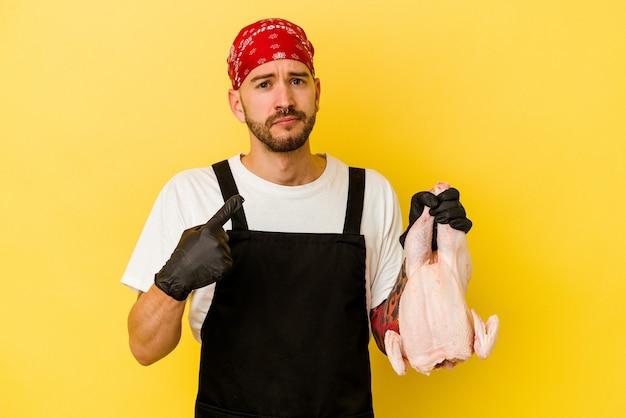 Jonge getatoeëerde batcher blanke man met een kip geïsoleerd op een gele achtergrond wijzend met de vinger naar je alsof uitnodigend dichterbij komen.
