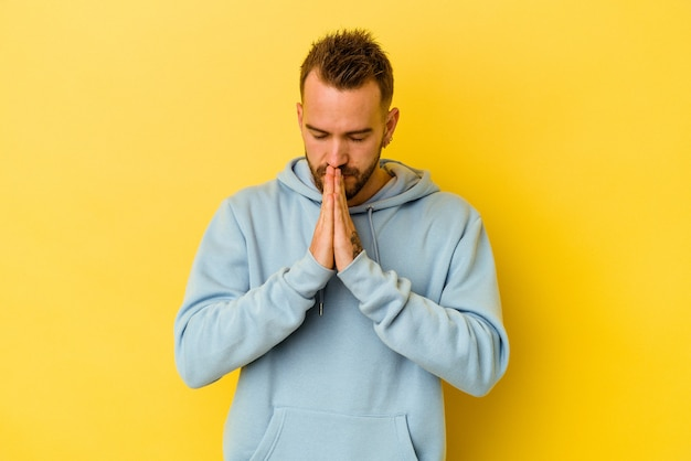 Jonge getatoeëerde blanke man geïsoleerd op gele achtergrond bidden, toewijding, religieuze persoon op zoek naar goddelijke inspiratie.