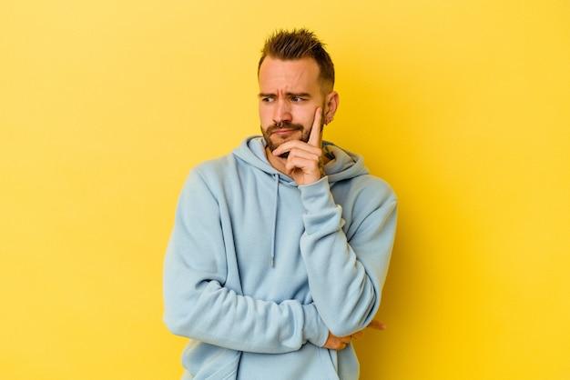Jonge getatoeëerde blanke man geïsoleerd op gele achtergrond overweegt, een strategie plannen, nadenken over de manier van een bedrijf.