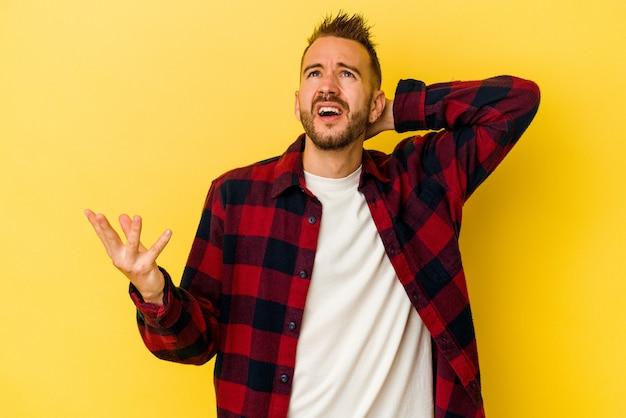 Jonge getatoeëerde blanke man geïsoleerd op gele achtergrond schreeuwen van woede.