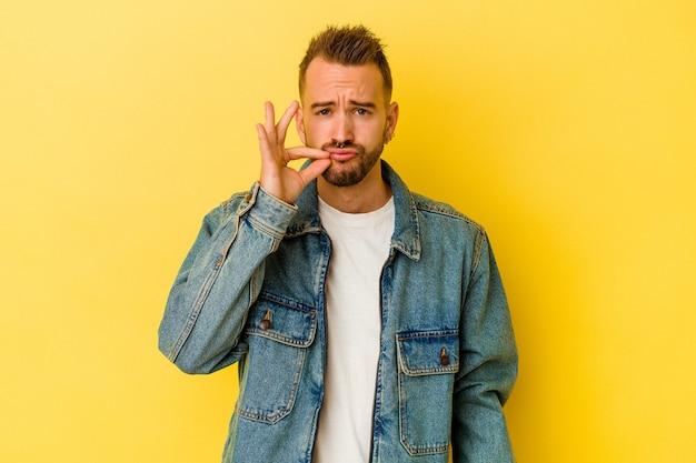 Jonge getatoeëerde blanke man geïsoleerd op gele muur met vingers op lippen die een geheim houden. Premium Foto