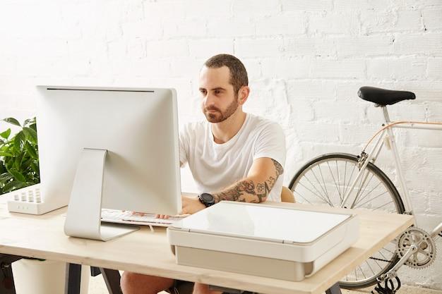 Jonge getatoeëerde freelancer man in leeg wit t-shirt werkt op zijn computer thuis in de buurt van zijn fiets, kijkend in display