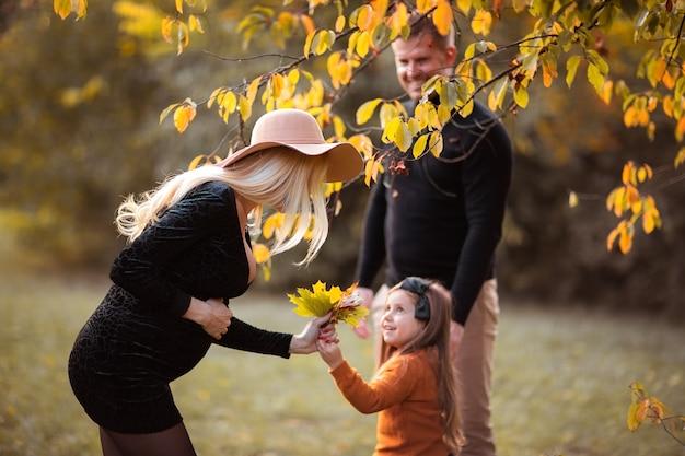 Jonge gezin van drie met zwangere mooie moeder, dochter en vader tijd samen doorbrengen