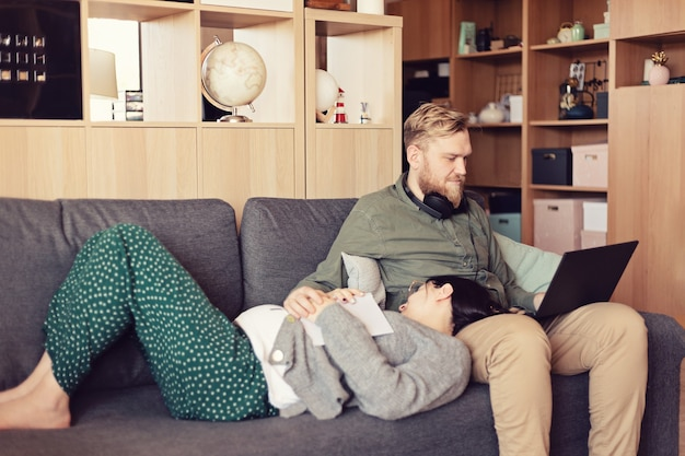 Jonge gezin, zwangere vrouw en man met laptop zittend op de bank in de woonkamer. werken in een informele omgeving, op afstand werken, thuiskantoor, freelancer, zelfisolatie, idee van uitstelgedrag