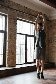 Jonge gezonde atletenmens die spieren uitrekken vóór training