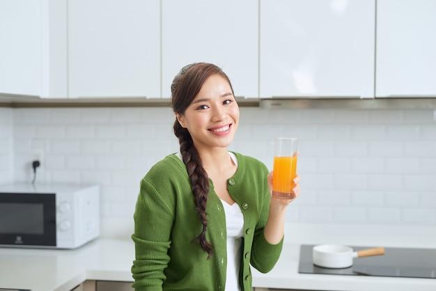Jonge gezonde aziatische vrouw die jus d'orange drinkt