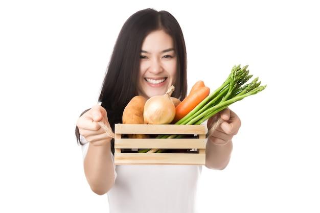 Jonge gezonde aziatische vrouw met verse biologische groente in mand die op wit wordt geïsoleerd.
