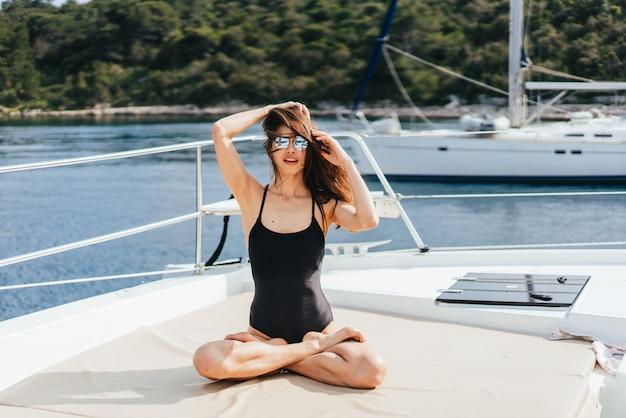 Jonge gezonde en kalme vrouw die yoga op varende jachtboot doen in overzees bij eiland