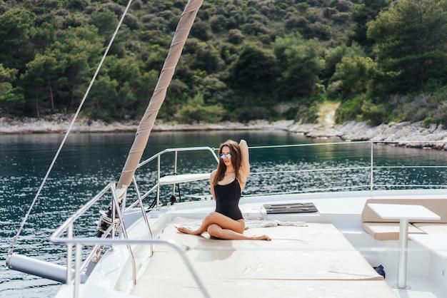 Jonge gezonde en kalme vrouw die yoga op varende jachtboot doen in overzees bij eilandachtergrond