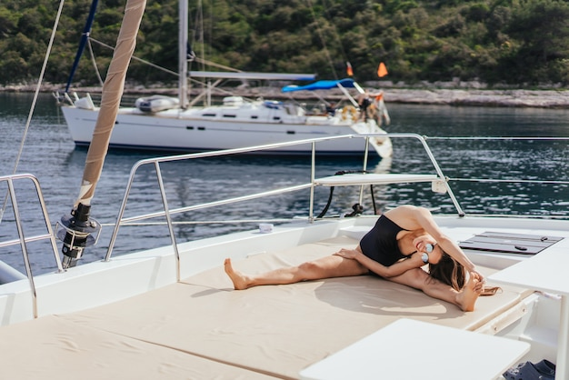 Jonge gezonde en kalme vrouw die yoga op varende jachtboot doen in overzees