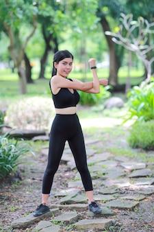 Jonge gezonde en sportieve vrouw doen yoga die zich openlucht uitrekken