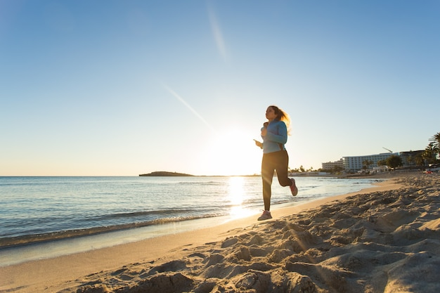 Jonge gezonde levensstijl fitness vrouw loopt bij zonsopgang strand.