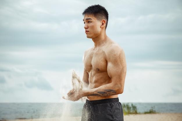 Jonge gezonde man atleet doen oefening op het strand. signle mannelijk model shirtless trainingslucht aan de rivierzijde in zonnige dag. concept van een gezonde levensstijl, sport, fitness, bodybuilding.