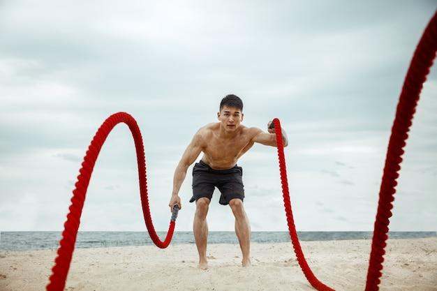 Jonge gezonde man atleet doen squats op het strand
