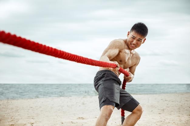 Jonge gezonde man atleet doet squats op het strand