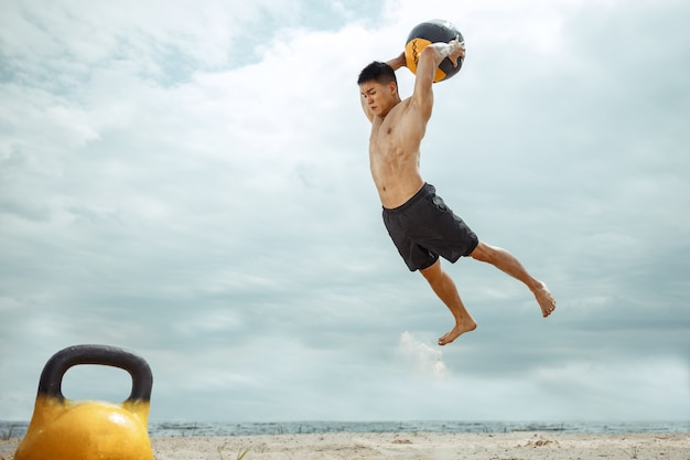 Jonge gezonde man atleet oefening met het gewicht en de bal op het strand. signle shirtless training voor mannelijk model aan de rivierzijde. concept van een gezonde levensstijl, sport, fitness, bodybuilding.