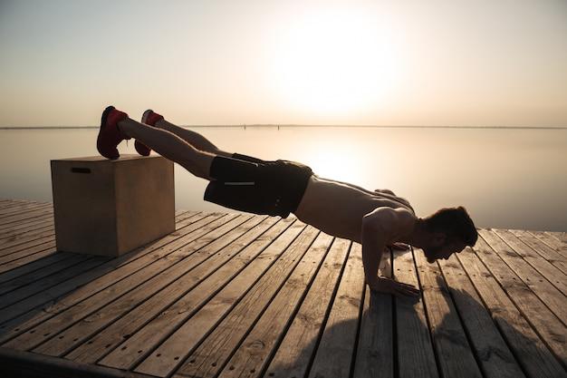 Jonge gezonde man doet push-ups met speciale apparatuur