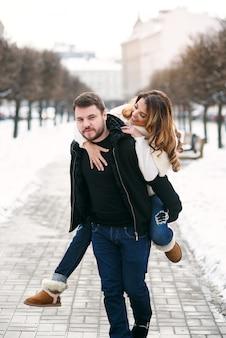 Jonge gezonde man houdt zijn mooie vriendin op de handen van de winter besneeuwde straat. nieuwjaar en kerstmis.