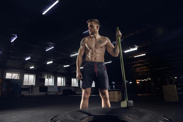 Jonge gezonde mannelijke atleet die oefeningen in de sportschool doet