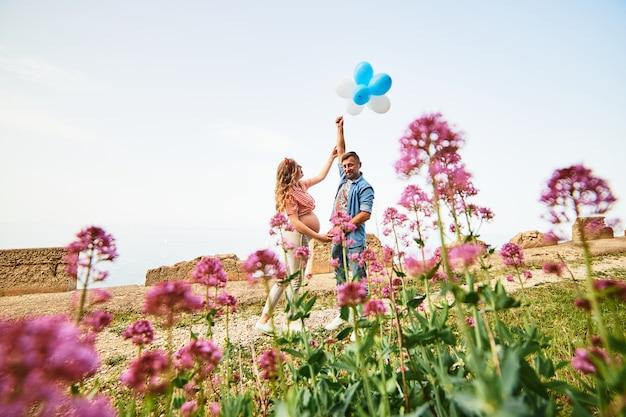Jonge gezonde schoonheids zwangere vrouw met haar echtgenoot en ballons in openlucht