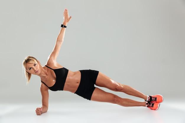 Jonge gezonde sportvrouw planking doen