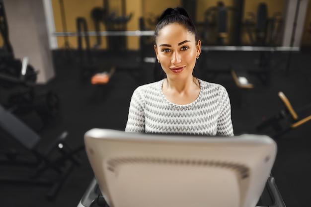 Jonge gezonde vrouw cardio op een loopband in de sportschool